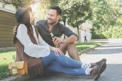 Jeunes couples se reposant en parc et tenant la bouteille de la boisson Photographie stock libre de droits