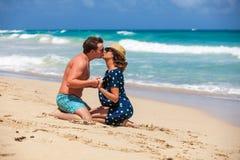 Jeunes couples se reposant ensemble sur un sable par l'océan Images libres de droits