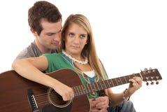 Jeunes couples se reposant jouant les visages paisibles de guitare Photo stock