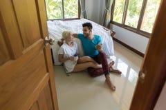 Jeunes couples se reposant près du lit, homme hispanique et femme de sourire heureux de matin à l'aide du téléphone intelligent d Images libres de droits
