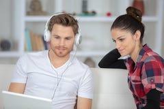 Jeunes couples se reposant sur l'Internet de sofa et de ressac Images libres de droits