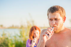 Jeunes couples se reposant sur la plage, cigarette électronique de tabagisme Images libres de droits