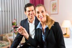 Jeunes couples se reposant sur le bâti dans la chambre d'hôtel Images libres de droits