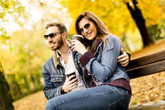 Jeunes couples se reposant sur le banc avec des tasses de café pendant l'automne Image stock