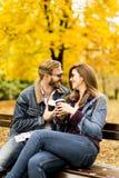 Jeunes couples se reposant sur le banc avec des tasses de café pendant l'automne Images stock