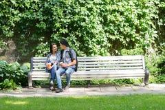 Jeunes couples se reposant sur le banc avec une tasse de café Image libre de droits