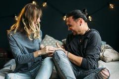 Jeunes couples se reposant sur le lit et riant tout en se chatouillant personnes heureuses de sourire Amie bouclée les gens dedan Photographie stock libre de droits