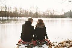 Jeunes couples se reposant sur le pilier au lac congelé regardant chaque othe Photos libres de droits