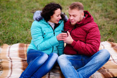 Jeunes couples se reposant sur le plaid et le café de boissons d'un thermo Photos libres de droits