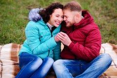 Jeunes couples se reposant sur le plaid et le café de boissons d'un thermo Photographie stock libre de droits