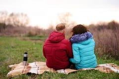 Jeunes couples se reposant sur le plaid et le café de boissons d'un thermo Photo libre de droits