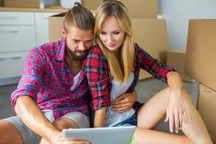 Jeunes couples se reposant sur le plancher avec le PC de comprimé et choisissant le fu images stock