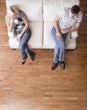 Jeunes couples se reposant sur le siège d'amour Photos stock