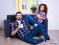 Jeunes couples se reposant sur le sofa avec des tasses de thé ou de café dans le livin Photo stock