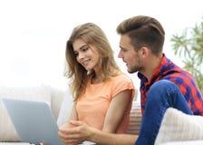 Jeunes couples se reposant sur le sofa et regardant des photos sur l'ordinateur portable Image libre de droits