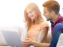 Jeunes couples se reposant sur le sofa et regardant des photos sur l'ordinateur portable Images libres de droits