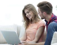 Jeunes couples se reposant sur le sofa et regardant des photos sur l'ordinateur portable Photos libres de droits