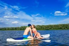 Jeunes couples se reposant sur le support vers le haut du baiser de panneau de palette Photo libre de droits