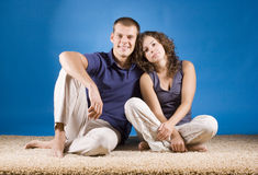 Jeunes couples se reposant sur le tapis beige photographie stock libre de droits