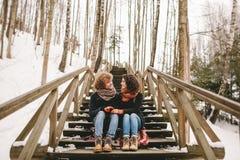 Jeunes couples se reposant sur les escaliers en bois dehors en hiver Photographie stock libre de droits