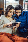 Jeunes couples se reposant sur Sofa Using Digital Tablet Photos stock