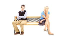 Jeunes couples se reposant sur un banc en bois ayant ensuite un argument photos stock