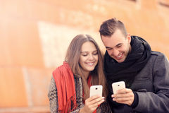 Jeunes couples se reposant sur un banc et à l'aide des smartphones Photo libre de droits