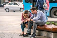 Jeunes couples se reposant sur un banc regardant leurs téléphones portables Photographie stock libre de droits