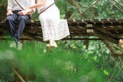 Jeunes couples se reposant sur un pont en bois dans une forêt Photos libres de droits