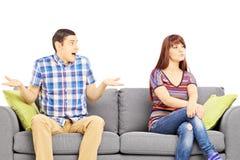Jeunes couples se reposant sur un sofa pendant un argument photo libre de droits