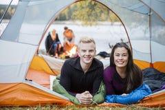 Jeunes couples se situant dans la tente pendant le camping de Lakeside Photo stock