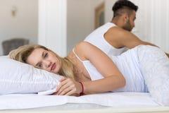 Jeunes couples se situant dans le lit, ayant le problème de conflit, les émotions négatives tristes homme hispanique et la femme photo stock