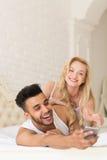 Jeunes couples se situant dans le lit, homme hispanique de sourire heureux à l'aide du téléphone intelligent de cellules, femme e Photo stock