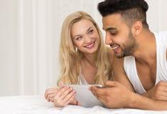 Jeunes couples se situant dans le lit, l'homme de sourire heureux et la femme hispaniques à l'aide de la tablette Image stock