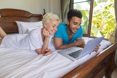 Jeunes couples se situant dans le lit, l'homme de sourire heureux et la femme hispaniques à l'aide de l'ordinateur portable Image libre de droits