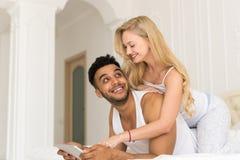 Jeunes couples se situant dans le lit, l'homme de sourire heureux et la femme hispaniques à l'aide du téléphone intelligent de ce Images stock