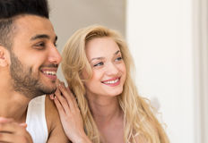 Jeunes couples se situant dans le lit, l'homme de sourire heureux et les amants hispaniques de femme dans la fin de chambre à cou Images stock