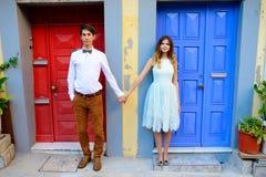 Jeunes couples se tenant à côté d'une porte bleue lumineuse photos libres de droits
