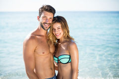 Jeunes couples se tenant avec le bras autour sur le rivage à la plage Photographie stock libre de droits