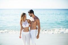Jeunes couples se tenant avec le bras autour sur le rivage Photographie stock libre de droits