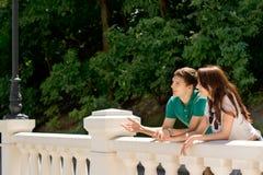 Jeunes couples se tenant causants sur un pont Images stock