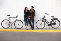 Jeunes couples se tenant contre le mur et étreindre photographie stock libre de droits