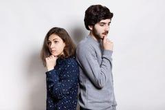 Jeunes couples se tenant de nouveau au dos tenant leurs mains sur le menton examinant la distance ayant l'expression triste pensa Image stock