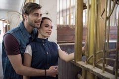Jeunes couples se tenant embrassants et regardants loin dans l'écurie Images libres de droits