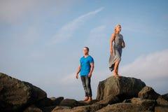 Jeunes couples se tenant sur des roches Photos stock