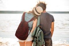 Jeunes couples se tenant vers l'arrière étreignants et regardants le bord de la mer Photographie stock