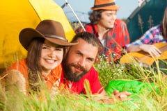 Jeunes couples se trouvant sur l'herbe à côté de leur tente Photographie stock