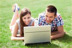 Jeunes couples se trouvant sur l'herbe avec l'ordinateur portatif Photographie stock libre de droits