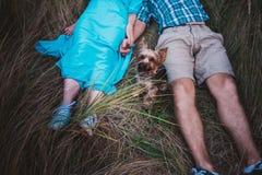 Jeunes couples se trouvant sur l'herbe tenant les mains et le petit chien entre eux Image libre de droits