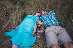 Jeunes couples se trouvant sur l'herbe tenant les mains et le petit chien entre eux Photos stock